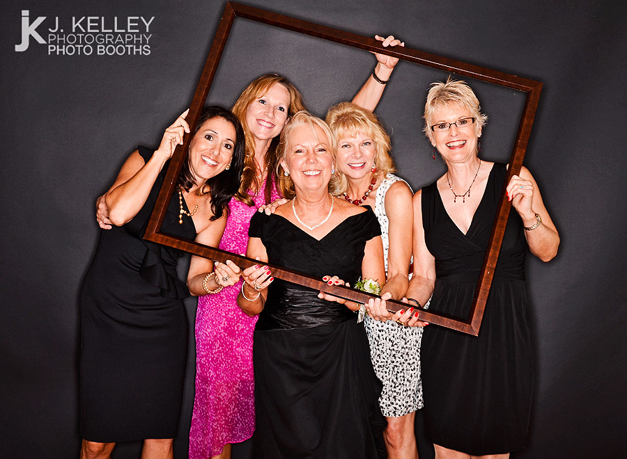 Women Pose With A Picture Frame In An Open Air Photo Booth At Wedding Reception