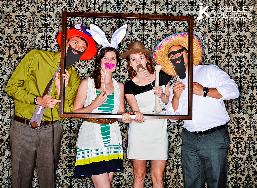 St. Louis Missouri wedding guests use a picture frame as a photo booth prop