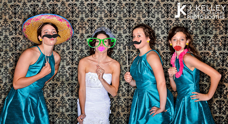 St. Louis Bride and bridesmaids take photographs in an open air photo booth at a wedding reception