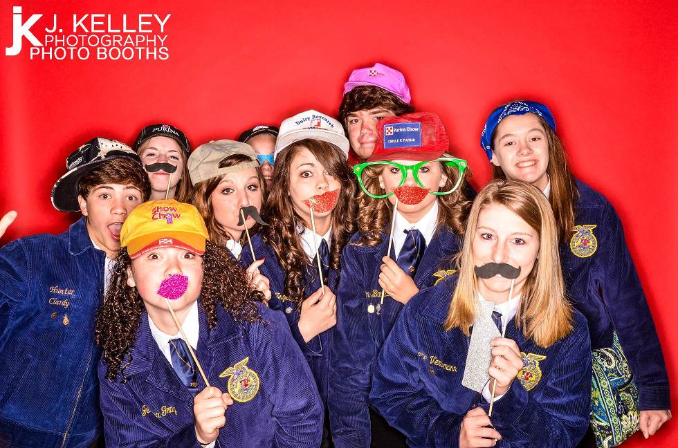 large group, photo booth fun, vibrant red backdrop