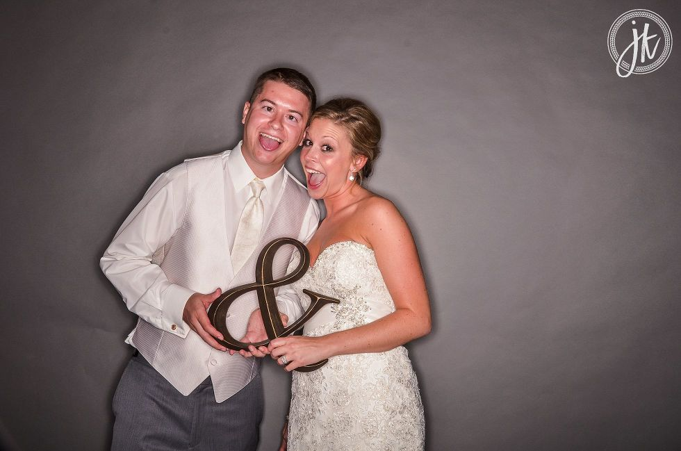 Bride and groom with an ampersand prop in the photo booth at their Jefferson City Wedding Reception